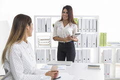 Two girls are in the office. One of them is happy. Businesswoman with brown hair is happy to see her supervisor and smiling broadly while holding a tablet Stock Photos