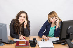 Two girls in the office talking on mobile phones Stock Photo