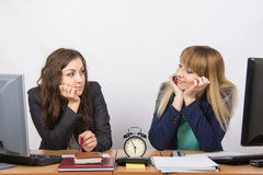 Two girls in the office waiting for the end of working hours on the clock and looking at each other Stock Photo
