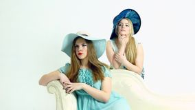 Two girls in old style hat posing. Two girlfriends in old style hat posing stock video footage