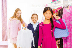 Two girls and one boy hold chosen clothes in store Stock Image