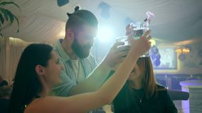 Two girls and one guy have fun in a club and make a toast with glasses in their hands. Two girls and one guy have fun in a nightclub and make a toast with stock video footage