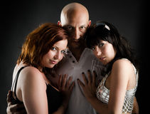 Two girls and one man in dark portrait Royalty Free Stock Image