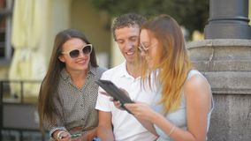 Two Girls and One Man with Notes, Pens and Tablet Spending Time Outside. Outdoors Portrait of Three Smiling Students stock footage