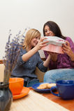 Two Girls Opening Present. Two young girls drinking coffee, having fun and opening present Stock Photography