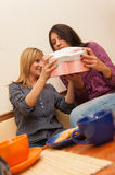 Two Girls Opening Present. Two young girls drinking coffee, having fun and talking Royalty Free Stock Photography