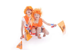 Two girls in orange outfit cheer. Two holland supporters in orange cheer against white background Royalty Free Stock Images