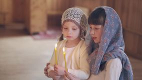 Two girls in the Orthodox Church holding candles. Two girls in the Orthodox Church holding candles stock video footage