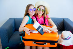 Two girls packing suitcases Stock Images