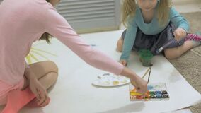 Two girls paint with watercolour paints and brushes on a large drawing paper on the floor, children's joint creativity.