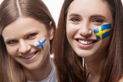 Two girls with painted flags on their face. With flag of Finland and flag of Sweden. Looking at the camera and smile Royalty Free Stock Photos