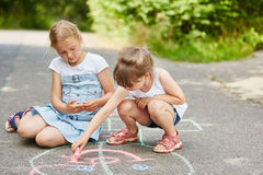 Two girls painting with chalk on floor Royalty Free Stock Photo