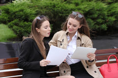 Two girls with papers and tablet computers talk on a park bench. Sunny day Stock Photos