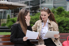Two girls with papers and tablet computers talk on a park bench. Sunny day Royalty Free Stock Photos