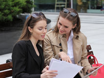 Two girls with papers and tablet computers talk on a park bench. Sunny day Stock Images