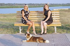 Two girls in a park on a bench Stock Images