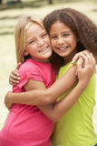 Two Girls In Park Giving Each Other Hug. Smiling At Camera Stock Photos