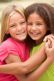 Two Girls In Park Giving Each Other Hug. Smiling At Camera Stock Photography