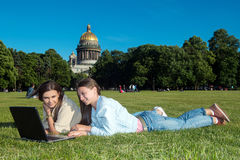 Two girls in the park with a laptop. Two friends with tablet computer sitting on the grass in the summer park. youth lifestyle Royalty Free Stock Image