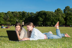 Two girls in the park with a laptop. Two friends with tablet computer sitting on the grass in the summer park. youth lifestyle Royalty Free Stock Photography