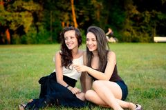 Two girls in park, one pointing to the other Royalty Free Stock Photography