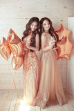Two Girls on party. Beautiful young women in elegant golden dres Stock Photography