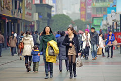 Two girls pass through a busy street Royalty Free Stock Images