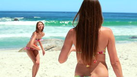 Two girls pass a friebee to each other. While at the beach stock footage