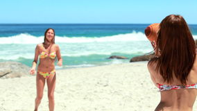 Two girls passing the football to each other. At the beach stock footage