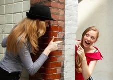 Two girls peeking around the w royalty free stock photo