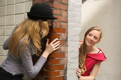 Two girls peeking around the wall. Two girls peeking around the two sides of the wall at house entrance Royalty Free Stock Image
