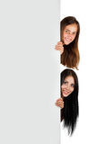 Two girls peeking from behind a poster Royalty Free Stock Images