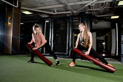Two girls perform exercises with sports equipment in the sport club