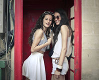Two girls in a phone box Royalty Free Stock Images