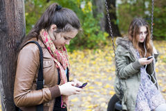 Two girls with phones Stock Photos