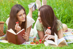 Two girls on picnic. Two beautiful girls on picnic eating strawberry while reading books stock photography