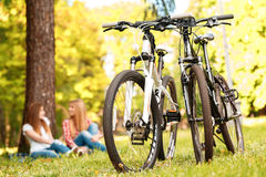 Two girls on a picnic with bikes. Selective focus on two sport bikes standing near while young beautiful girls with long hair sitting on a blue checkered mat Stock Photos