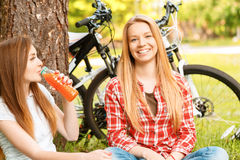 Two girls on a picnic with bikes. What a wonderful picnic. Two young beautiful girls with long hair sitting on a blue checkered mat under a tree smiling and Royalty Free Stock Photos