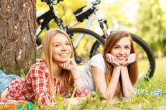 Two girls on a picnic with bikes. Two young beautiful girls with long hair lying on a blue checkered mat under a tree propping chins with their hands smiling Stock Images