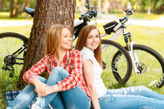 Two girls on a picnic with bikes. Two young beautiful girls with long hair sitting back to back on a blue checkered mat under a tree smiling happily, their bikes Royalty Free Stock Photos