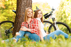 Two girls on a picnic with bikes. Two young beautiful girls with long hair sitting back to back on a blue checkered mat under a tree smiling happily, their bikes Stock Photography