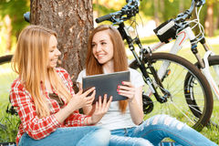 Two girls on a picnic with bikes. Two young beautiful girls with long hair sitting on a blue checkered mat under a tree looking at the tablet in their hands and Stock Photo