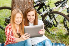 Two girls on a picnic with bikes. Two young beautiful girls with long hair sitting on a blue checkered mat under a tree making selfie with a tablet holding it Royalty Free Stock Images
