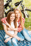 Two girls on a picnic with bikes. Two young beautiful girls with long hair sitting on a blue checkered mat under a tree smiling happily and hugging, their bikes Stock Photography