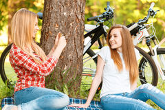 Two girls on a picnic with bikes. Young girl with long blond hair making a photo of her smiling friend while both are sitting on a blue checkered mat under a Royalty Free Stock Image