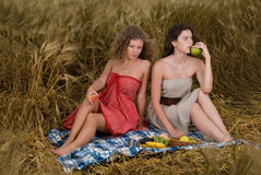 Two girls on picnic in wheat field Stock Images