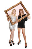 Two girls with picture frame. Stock Photo