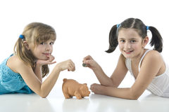 Two girls and piggy bank Royalty Free Stock Image