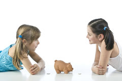 Two girls and piggy bank Stock Photography