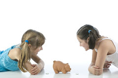 Two girls and piggy bank Stock Image